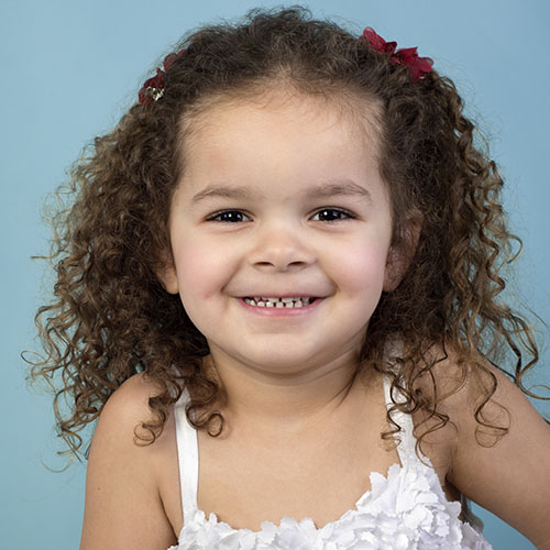 Adorable smiling mixed race toddler girl with curls at a Preschool & Daycare Serving El Cajon, Lakeside and Santee CA