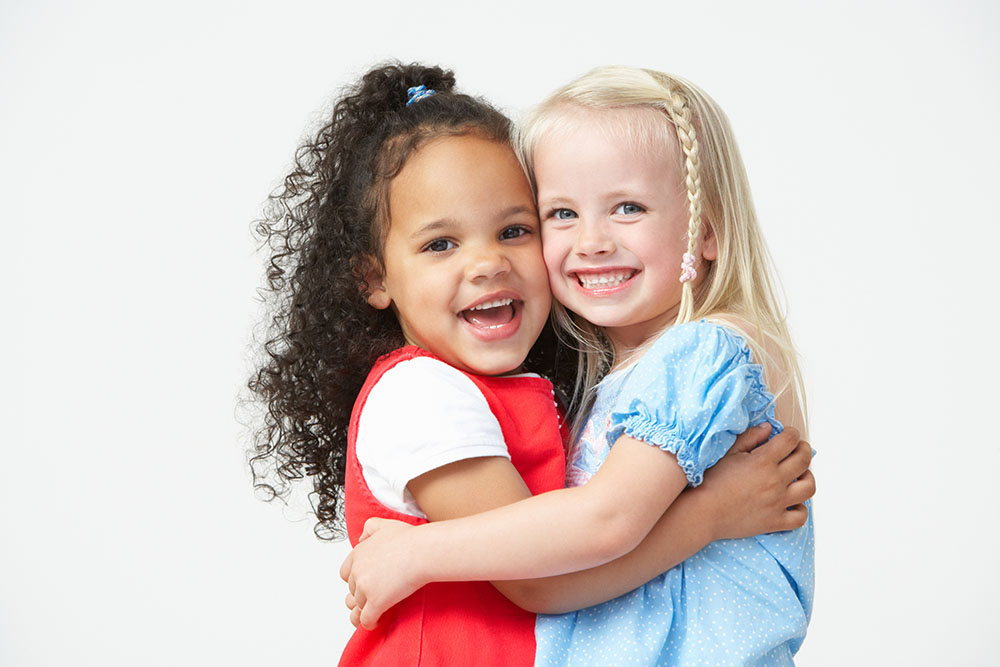 Two Pre School Girls Hugging One Another at a Preschool & Daycare Serving El Cajon, Lakeside and Santee CA
