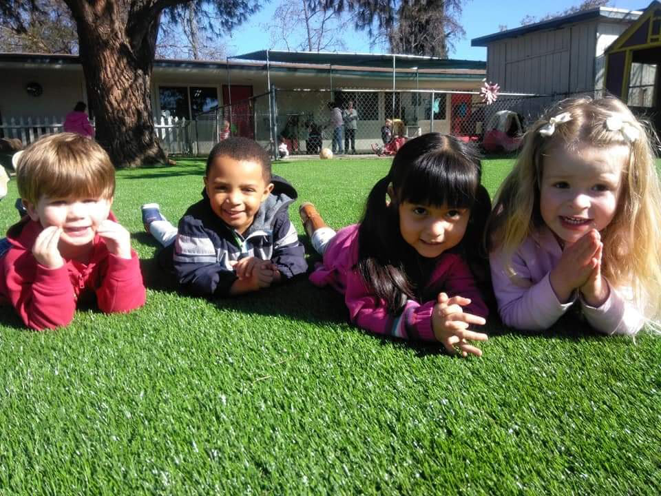children lying on grass outside at a Preschool & Daycare Serving El Cajon, Lakeside and Santee CA