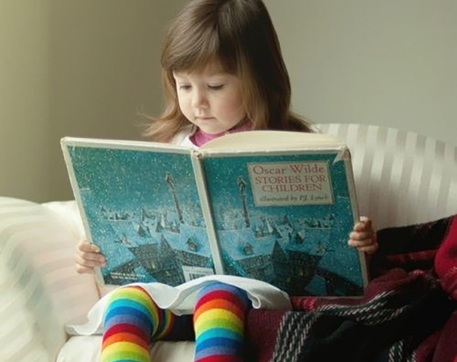cute little girl reading a book at a Preschool & Daycare Serving El Cajon, Lakeside and Santee CA
