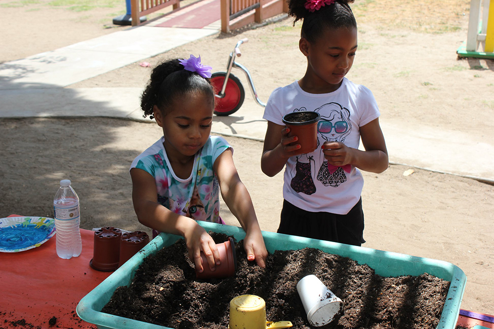 happy girls planting at a Preschool & Daycare Serving El Cajon, Lakeside and Santee CA